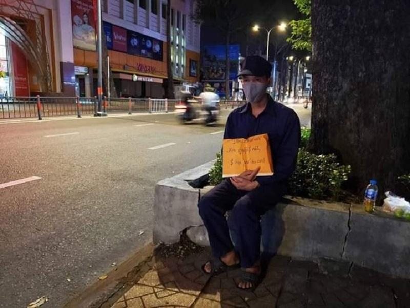 Mất việc do dịch, anh Trần Văn Lượm (40 tuổi, quê Hậu Giang) cầm bảng xin tiền đóng trọ, trả học phí cho con